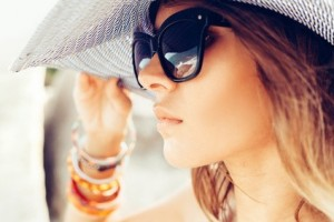 Close-up of face of young summer sexy woman wearing hat  and sunglasses. Outdoors lifestyle portrait